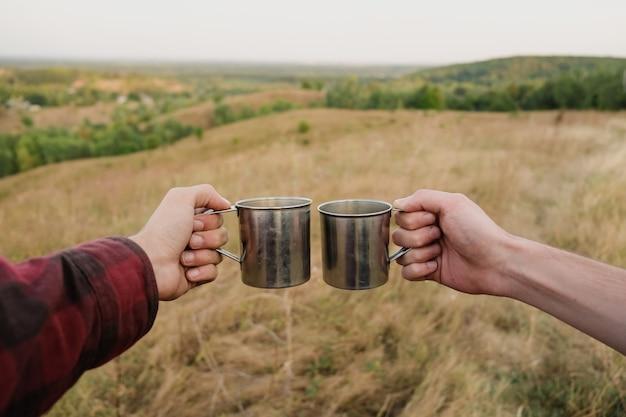 Zwei hände, die touristische metallkappen in der schönen natur halten. männer, die getränke auf dem hügel bei einer wanderung salutieren