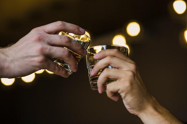 Zwei hände, die whisky gegen belichteten hintergrund rösten