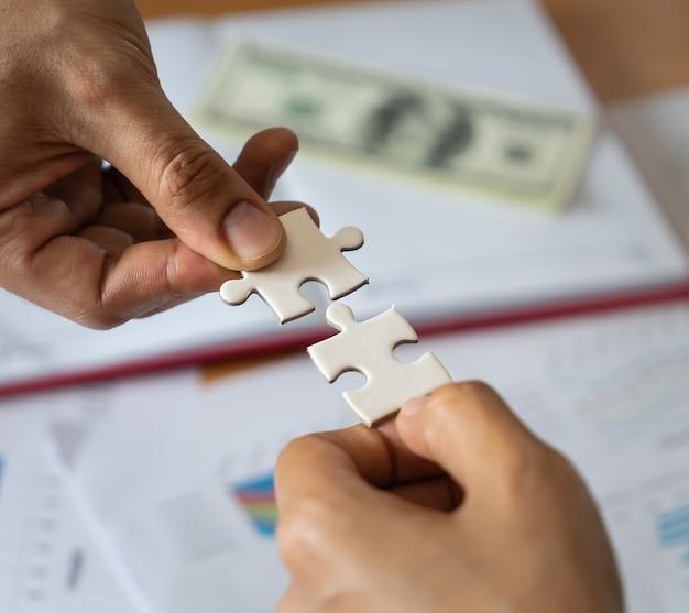 Zwei hände, die zusammen zwei puzzles zusammenfügen