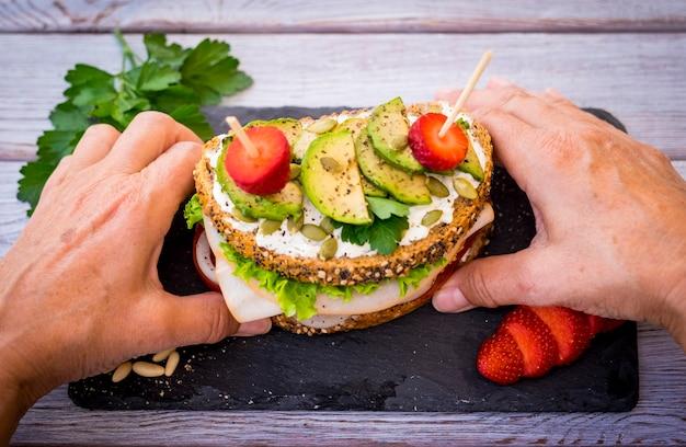 Zwei hände halten ein dreischichtiges vollkornsandwich mit gebratenem truthahn mit salat und tomate