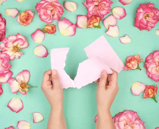 Zwei hände halten ein leeres rosa blatt, das aus dem notizbuch gerissen wurde