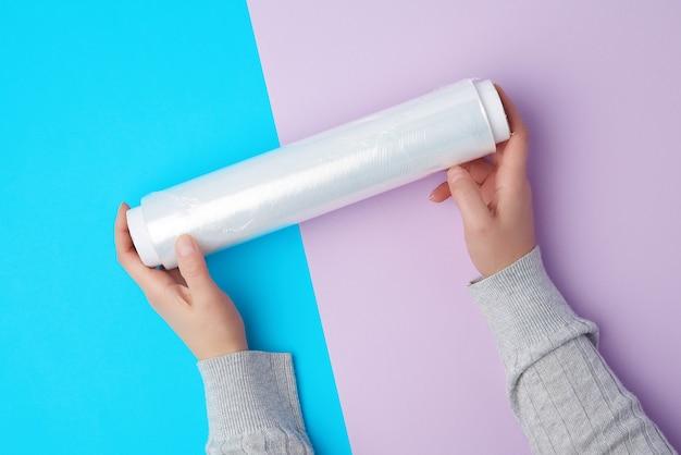 Zwei hände halten eine große rolle aufgewickelter weißer transparenter folie