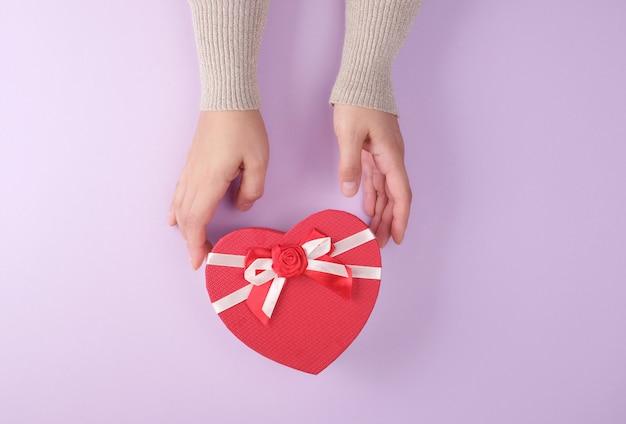 Zwei hände halten einen geschlossenen roten papierkasten in form eines herzens