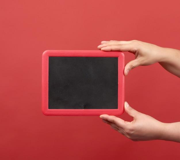 Zwei hände halten einen leeren rahmen auf einem roten hintergrund