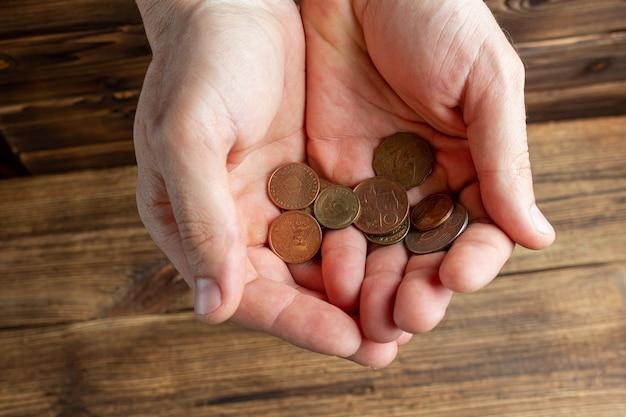 Zwei hände halten einige münzen in den handflächen