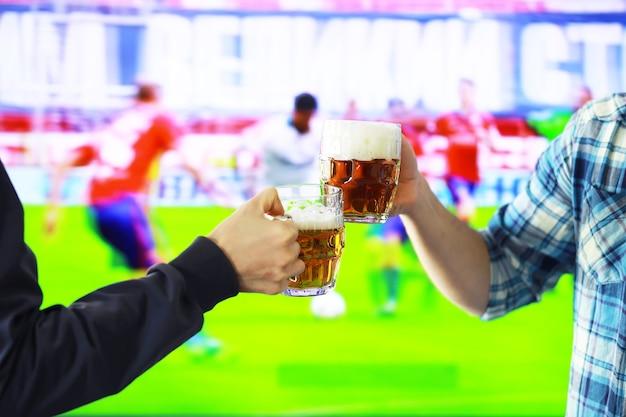 Zwei hände horizontal, die lagerbierglas halten und auf dem hintergrund des fußballspiels klirren