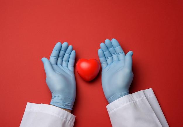 Zwei hände in blauen latexhandschuhen, die ein rotes herz halten, spendenkonzept, draufsicht