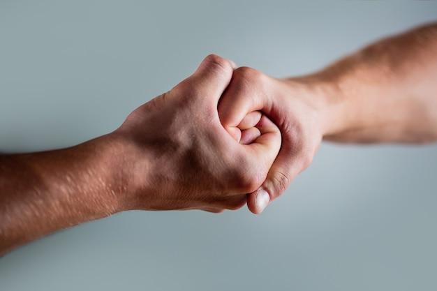 Zwei hände, isolierter arm, helfende hand eines freundes. händedruck, arme. freundlicher händedruck, begrüßung durch freunde. rettung, helfende hand. männliche hand im händedruck vereint. mann helfen hände, vormundschaft, schutz.