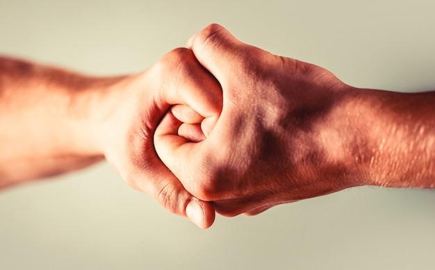 Zwei hände, isolierter arm, helfende hand eines freundes. händedruck, arme. freundlicher händedruck, freunde grüßen. rettung, helfende hand. männliche hand im händedruck vereint. mann hilft hände, vormundschaft, schutz