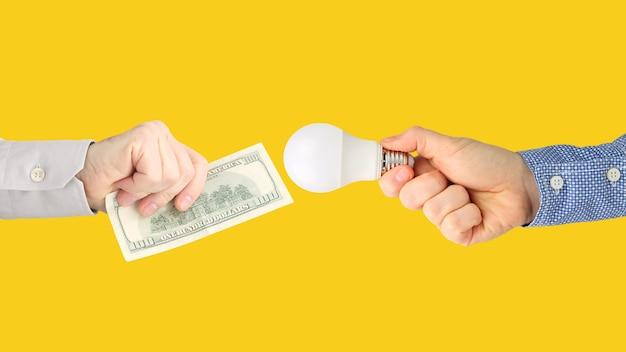 Zwei hände mit dollarnoten und einer led-lampe auf einem hellen orange hintergrund. bezahlung für strom. led-lampe kaufen. wirtschaftsbranche