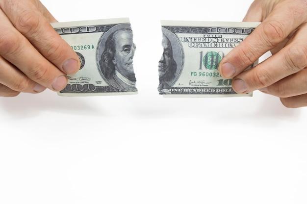 Zwei hände rissen einen hundert-dollar-schein in zwei teile auf weißem grund.