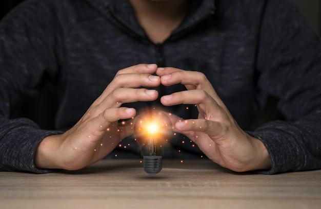 Zwei hände schützen die glühbirne, die auf dem tisch leuchtet