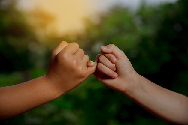 Zwei hände verhaken sich gegenseitig das kleine fingerkonzept des versprechens