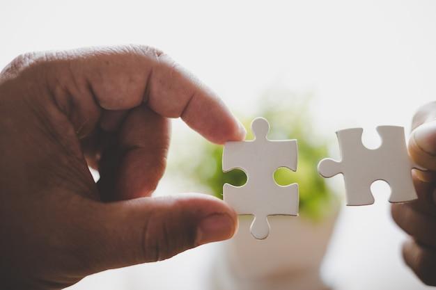 Zwei hände versuchen, paar puzzleteil zu verbinden. ein teil des ganzen.