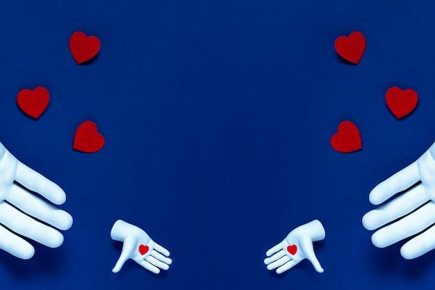 Zwei hände werfen rote herzen auf blauem grund. das konzept zum valentinstag
