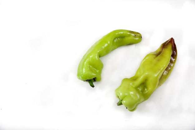 Zwei hässliche lustige grüne paprika lokalisiert auf weißem hintergrund. vegetarisches lebensmittelkonzept. speicherplatz kopieren.