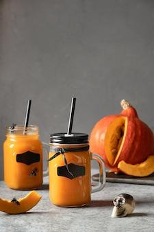 Zwei halloween-cocktails mit kürbissaft garnieren schädel und spinnen für festliche party auf grau