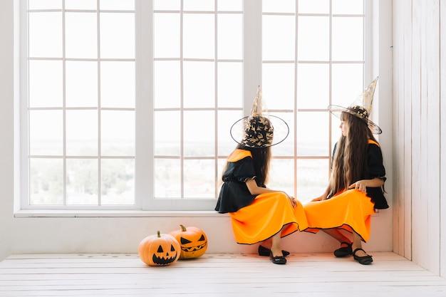 Zwei halloween-hexen, die am fenster die hauptrolle spielen
