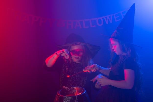 Zwei halloween-hexen, die einen trank machen und in halloween-nacht-magie-feiertagen und mystikern beschwören