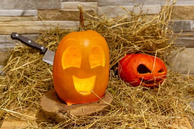 Zwei halloween-kürbisse liegen auf einem heu vor dem hintergrund einer steinmauer