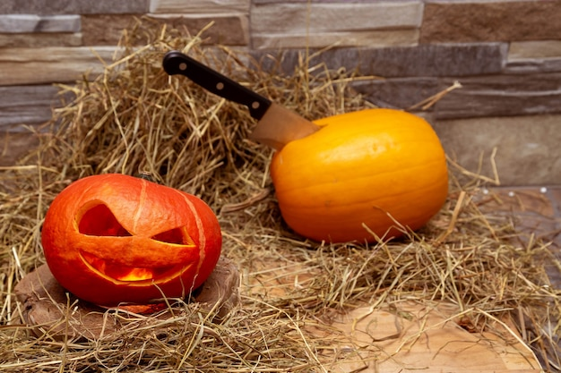 Zwei halloween-kürbisse liegen auf einem heu vor dem hintergrund eines steinmauermessers im gelben kürbis