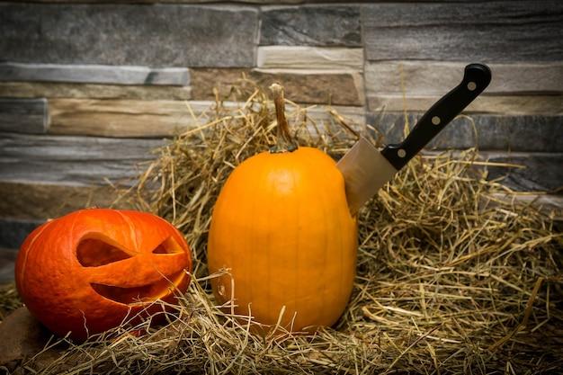 Zwei halloween-kürbisse liegen auf heu vor dem hintergrund eines steinmauermessers, das im gelben kürbis steckt