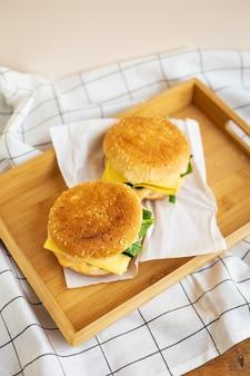 Zwei hamburger liegen auf einem holztablett mit einer weißen serviette, nahaufnahme, draufsicht.