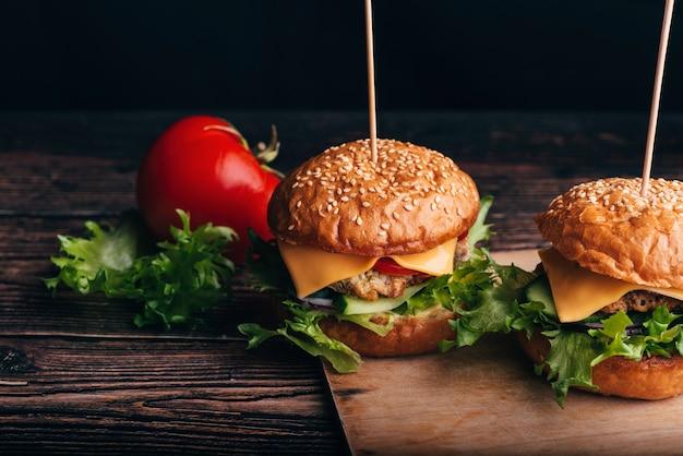 Zwei hamburger mit fleisch, käse, salat, tomaten auf einem brett
