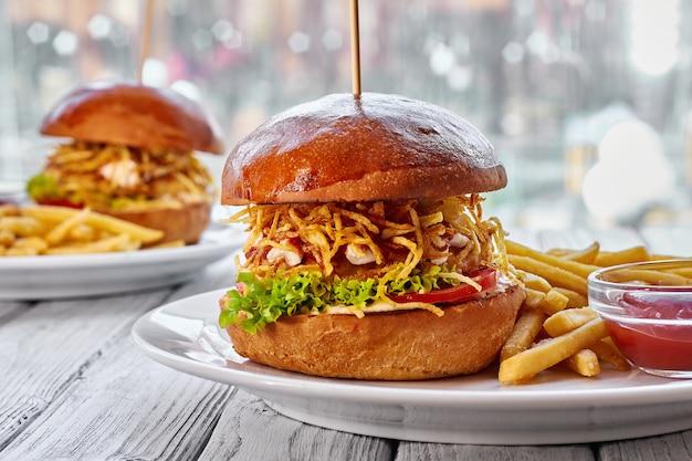 Zwei hamburger mit hähnchenschnitzel, käse, pommes frites, tomaten, salat, sauce und ketchup