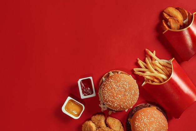Zwei hamburger und pommes-frites-saucen auf rotem hintergrund fast-food-draufsicht
