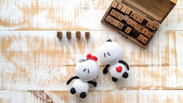 Zwei handgemachte gestrickte spielzeuge und ein hölzerner satz von buchstaben, die wort zusammensetzen. draufsicht