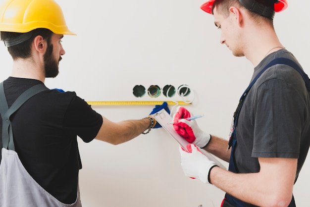 Zwei handwerker, die maßnahmen treffen