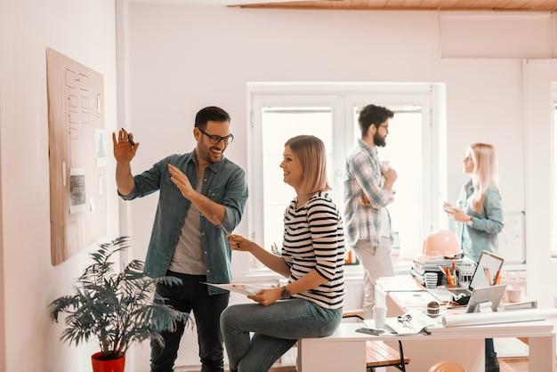 Zwei hart arbeitende junge kollegen, die im büro einen geschäftsplan entwickeln