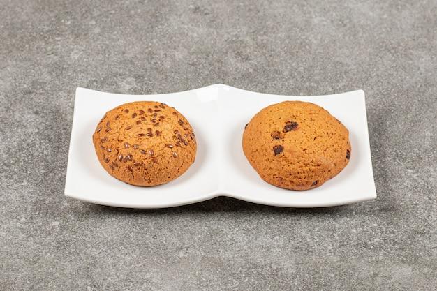 Zwei hausgemachte frische kekse auf weißem teller.