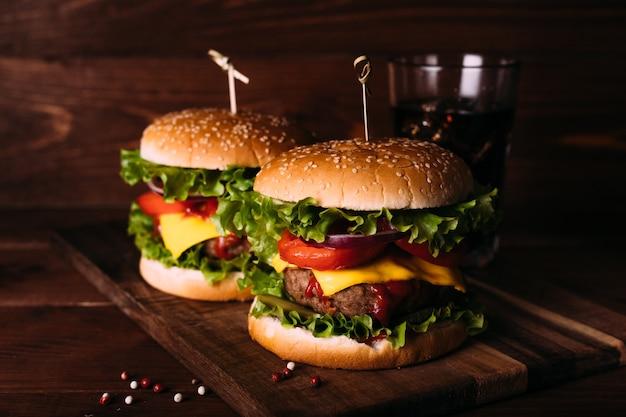 Zwei hausgemachte frische leckere burger mit salat und käse auf rustikalem holztisch. pommes frites, tomaten und sauce. dunkler nahrungsmittelhintergrund.