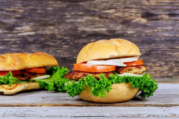 Zwei hausgemachte gegrillte hamburger mit rindfleisch, zwiebeln, tomaten, salat und käse.