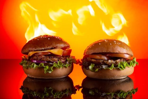 Zwei hausgemachte hamburger mit rindfleisch und gurken in brand