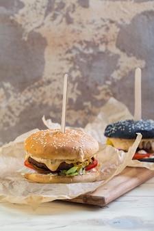 Zwei hausgemachte rindfleischburger mit dunklem und hellem brötchen, mit gemüse, roten zwiebeln, tomaten, eingelegten gurken und käse in pergament auf holzschneidebrett