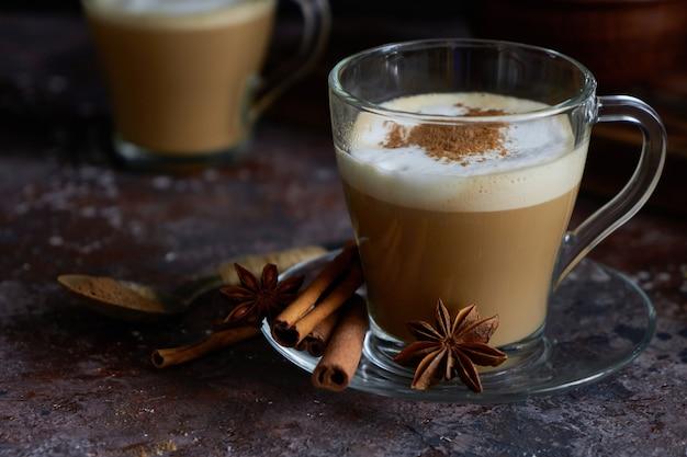Zwei heiße cappuccino-kaffee mit schaum, zimt, zucker und anis auf einer braunen oberfläche
