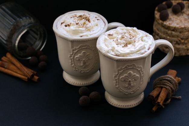 Zwei heiße kaffees mit schlagsahne und zimt mit pralinen auf dunklem hintergrund