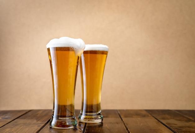 Zwei helle biergläser w auf der hellgelben oberfläche