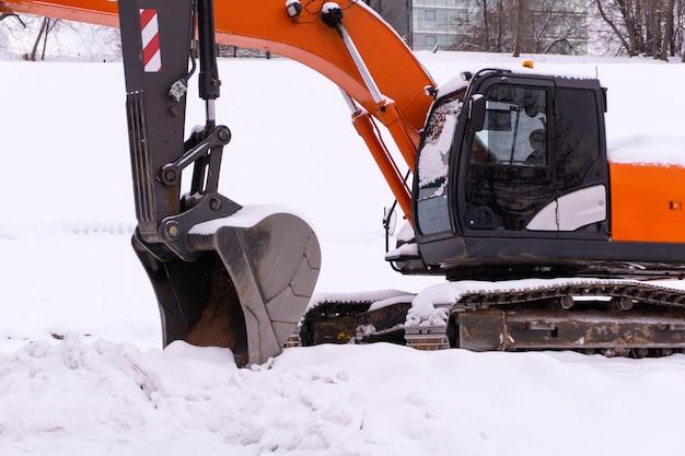 Zwei helle raupenbagger parken auf einem verschneiten feld, ausleger und stiele bilden eine enfilade