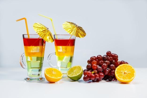 Zwei helle sommercocktails in einem glas und obst