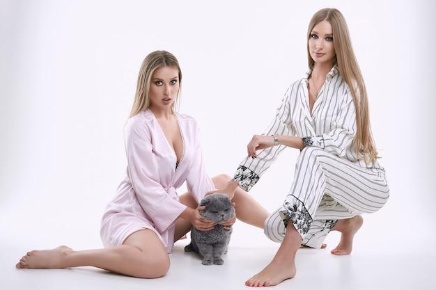 Zwei herrliche vorbildliche mädchen in den pyjamas, die mit einer fetten stammbaumkatze aufwerfen