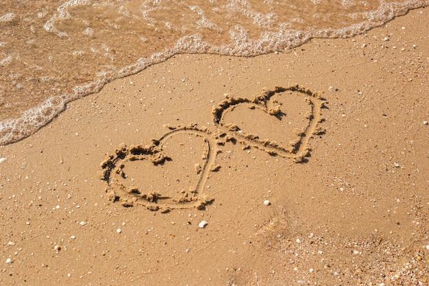 Zwei herzen an einem sandstrand gezeichnet. ansicht von oben, flach.