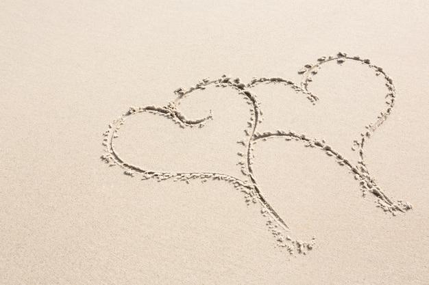 Zwei herzen formen auf sand gezeichnet