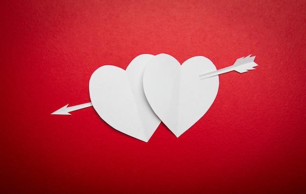 Zwei herzen papier durchbohrt mit einem pfeil-symbol für den valentinstag