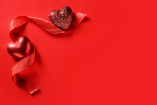 Zwei herzen und ein rotes band auf einem roten hintergrund mit kopienraum. valentinstagskarte. Premium Fotos