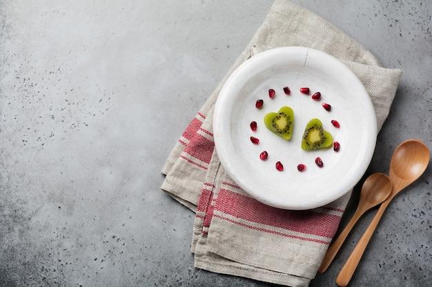 Zwei herzen von kiwi auf einer weißen keramikplatte auf einem grauen beton. postkarte zum valentinstag