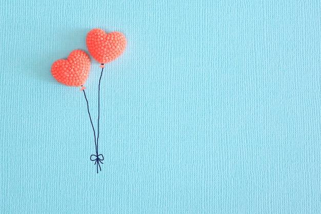 Zwei herzen von korallenfarbe auf blauem papier in form von ballons. kopieren sie platz.